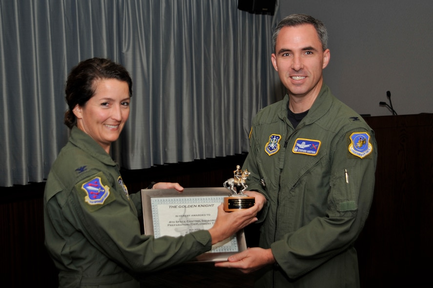 Col. Stephen Whiting, 21st Space Wing commander, presented the Golden Knight Award for May to the 4th Space Control Squadron preparation/deployment team, for deploying critical assets to the AOR. Col. Nina Armagno, 21st Operations Group commander, accepted the award on behalf of the squadron. The 4th SPCS, located at Holloman Air Force Base, N.M., provides combat space superiority effects to the commander of Joint Functional Component Command - Space (JFCC - Space) and theater combatant commanders. The squadron is one of the 21st Space Wing's geographically separated units. (Air Force photo by Robb Lingley)