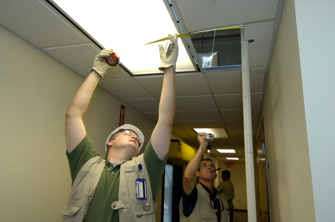 Chad Williams, left, and Harold Keck perform a building inspection. The two were part of an 11-person facility inspection team, from the 72nd Maintenance Engineering Office,  combs over a Tinker Building. They are inventorying and cataloguing anything and everything about the building. The look at everything from water fountains to roof access, documenting everything that needs repair now or in the future. The team inspects more than 3 million square feet per year. (Air Force photo by Margo Wright)