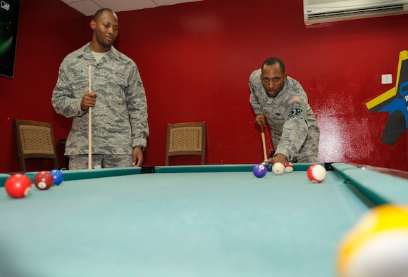SOUTHWEST ASIA – Staff Sgt. Bryant Preston, 380th Expeditionary Security Forces Squadron, plays a game of pool with his twin brother, Senior Airman Erik Preston, 380th Expeditionary Logistics Readiness Squadron, while on his lunch break here recently. The brothers met at the 380th Air Expeditionary Wing for the first time in more than three years. (U.S. Air Force photo/Senior Airman Stephen Linch)