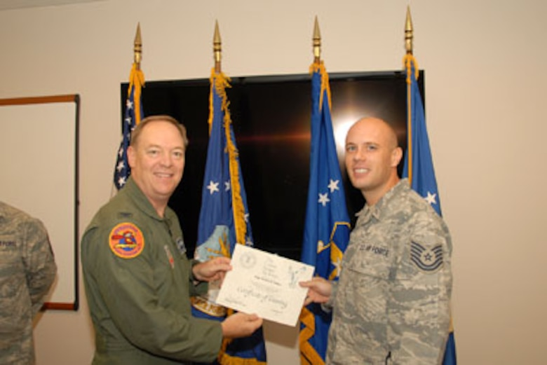 Col. Kevin W. Bradley, 174FW Commander presents Technical Sgt. Steven Sobus with his certificate on the 24th of September as part of the first graduating class of the Ground Control Station maintenance course held here at Hancock Field Air National Guard Base. (U. S. Air Force photo by Staff Sgt. Barbara Olney/RELEASED)