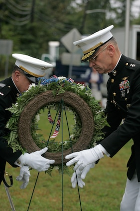 Chief Warrant Officer Nick D'Andrea, special operations officer, and Lt. Gen. Duane D. Thiessen, Deputy Commandant for Programs and Resources carry a wreath to the John Basilone Statue in Raritan, N.J., Sept 27. The celebration of the town's Medal of Honor recipient is the largest military parade in the nation.(Marine Corps photo by Sgt. Randall A. Clinton)