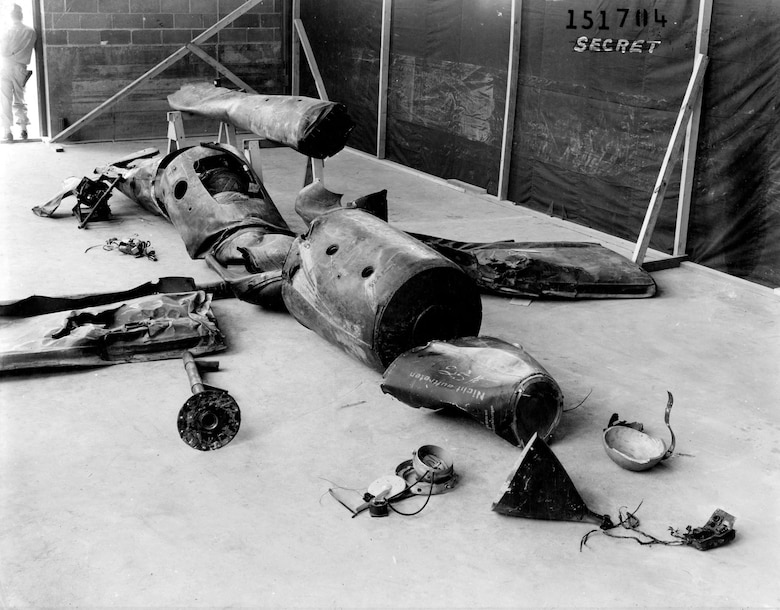 """Parts of downed V-1s were assembled and studied closely. Note the armed guard at the upper left and """"SECRET"""" stamp on upper right. (U.S. Air Force photo)"""