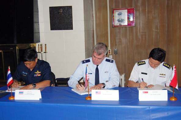 "Group Capt. Supijjaran Thamwatharsaree, Royal Thai Air Force; Col. Robert ""Randy"" Huston, 624th Regional Support Group; and Col. Lim Tuang Liang, Republic of Singapore Air Force sign the conference minutes which put the final touches on the flight schedule and the large force employment plan for the upcoming Cope Tiger exercise in Thailand in March 2010 at a conference held Sept 21-25 at Elmendorf Air Force Base, Alaska. Cope Tiger is an annual, multilateral aerial exercise which divides Thai, Singaporean and U.S. Air Force, Navy and Marine Corps aircraft into two mixed groups, pitting them against each other in a mock battle. The exercise also includes a two-phase humanitarian and civic assistance portion (Courtesy photo)"