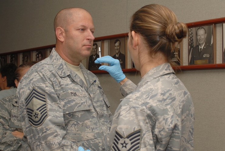 GOODFELLOW AIR FORCE BASE, Texas -- Chief Master Sgt. Robert Puhl, 17th Training Group chief enlisted manager, receives the FluMist from Tech Sgt. Nicole Melius, 17th Medical Group, Sept. 29, 2009. The FluMist is a live, but weakened, influenza virus that is sprayed into the nostrils as opposed to the flu shot, a dead virus, that is injected into the muscle. (U.S. Air Force photo/Staff Sgt. Laura R. McFarlane)
