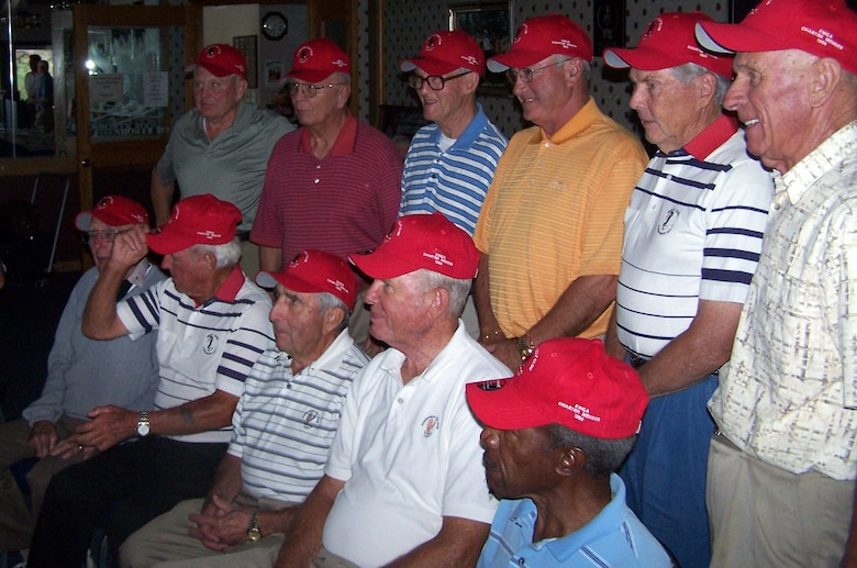 "Charter members of the Eisenhower Men's Golf Association pose for a group photo after receiving their red Eisenhower Golf Club hats bearing the label ""EMGA Charter Member 1988"" at the U.S. Air Force Academy Sept. 17, 2009. Out of 205 original EMGA members, 16 still actively play golf and were recognized at the luncheon for their stamina and continued athleticism. (U.S. Air Force photo/Butch Wehry)"