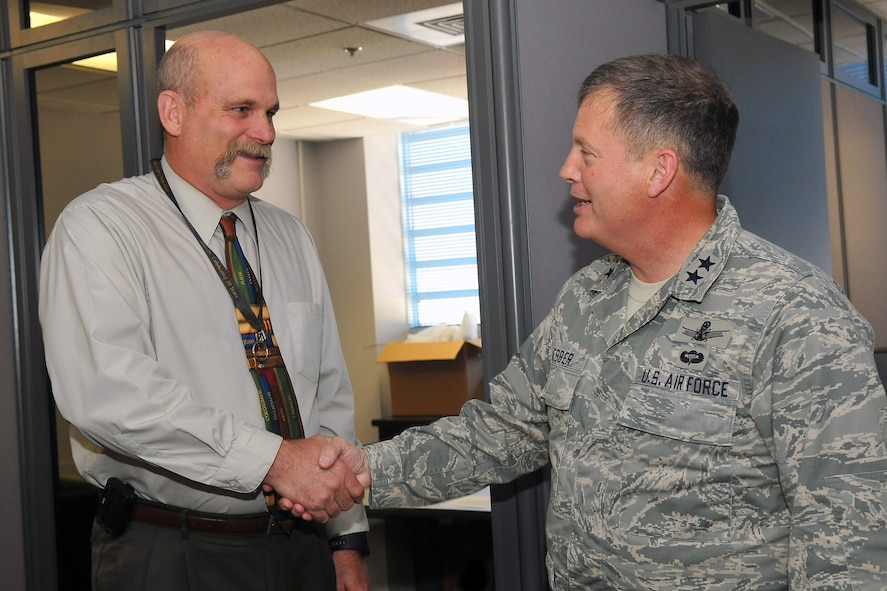 Maj. Gen. Richard Webber, 24th Air Force commander recognizes Kameron Thornburg, 688th Information Operations Wing with a coin March 31 for providing finance and Defense Travel System expertise to 24th Air Force prior to and during the stand of the NAF. He also trained new personnel upon their arrival ensuring a seamless transition to 24th AF. (US Air Force photo by Ted Koniares)