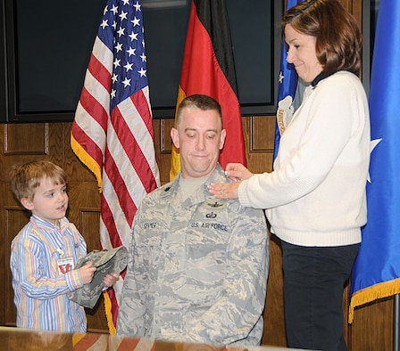 Lt. Col. Thomas Kramer receives assistance from his son Eli and wife Angela, in pinning on his new rank to lieutenant colonel during his promotion ceremony Mar. 31. Colonel Kramer is the 17th Air Force Chief of Global Force Management in the Operations Directorate (A3). (U.S. Air Force photo by Staff Sgt. Stefanie Torres)