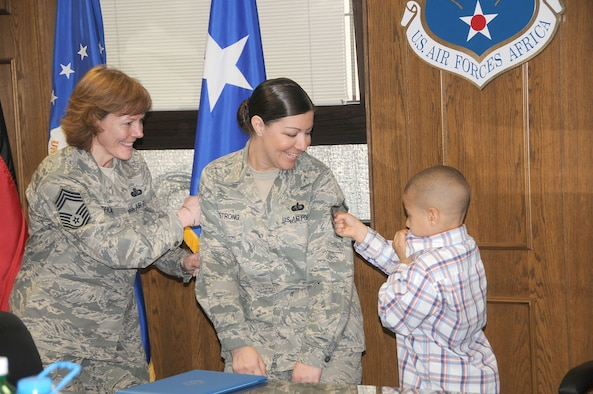 Master Sgt. Amanda Armstrong receives help tacking on her master sergeant stripes from her son Esteban, and from Chief Master Sgt. Karen Thomas, during her promotion ceremony Mar. 31. Master Sgt. Armstrong's husband, who is deployed, watched via Video Teleconference. Chief Thomas is the U.S. Air Forces Europe command services functional manager and Master Sgt. Armstrong is the 17th Air Force NCO in charge of services readiness. (U.S. Air Force photo by Staff Sgt. Stefanie Torres)