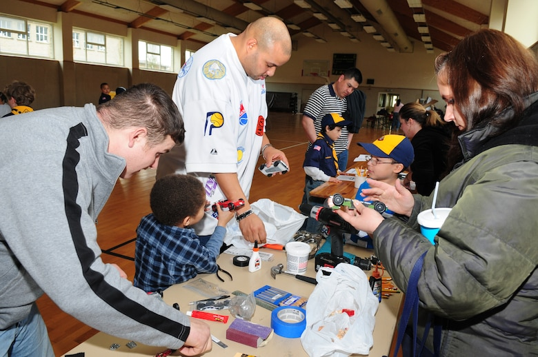 BITBURG ANNEX, Germany -- Boy Scout pack 161 and their family members fine-tune pinewood derby cars during the annual Pinewood Derby registration March 27.  The vehicles are weighed to meet requirements and placed on display prior to the race. (U.S. Air Force photo/Staff Sgt. Heather M. Norris)