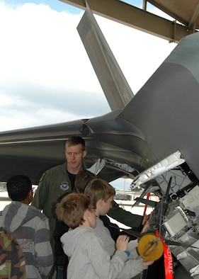 Capt. Scott Bradley, 43rd Fighter Squadron pilot, gives a tour of an F-22 Raptor to children from the Taunton Family Children's Home. The group toured Tyndall Air Force Base, Fla., March 26 during their spring break to see the Air Force in action. (U.S. Air Force photo/ Ashley M. Wright)