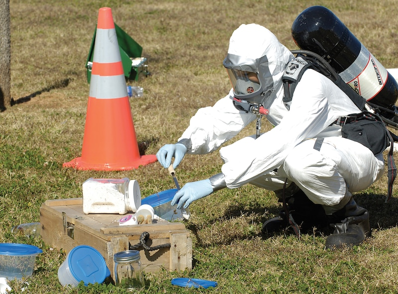 Bioenvironmental Engineering Flight personnel are called when the identity and threat level of an unknown substance needs to be identified during emergencies. While a wide protective area is secured around an exercise scene, as in a real life emergency, samples of the suspicious substance are gathered for testing by flight personnel in protective gear. (Air Force photo by Margo Wright)