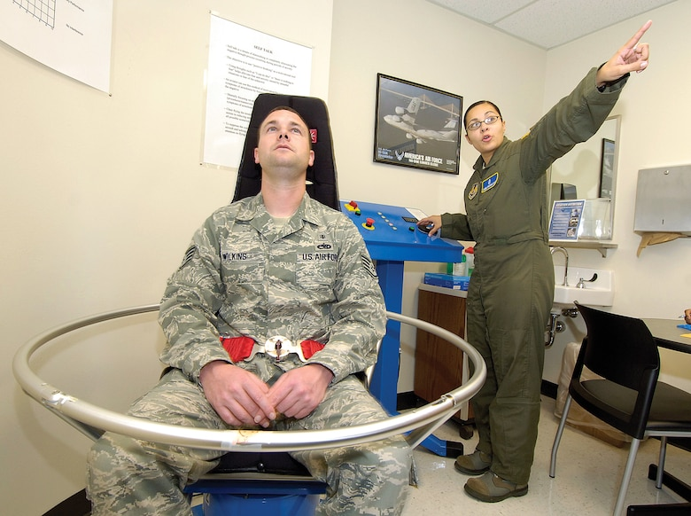 Teaching flight crew members how to handle airsickness is a responsibility of Flight Medicine.  A Barany chair spins a crew member poised in various positions to simulate motions during flight.  Staff Sgt. Isabel Brooks, the NCOIC of Human Performance, instructs the person to focus on a fixed point during a spin in the chair.  Overcoming motion sickness is vital for air crews, teaching them to trust their instruments and not what the human senses tell them. (Air Force photo by Margo Wright)