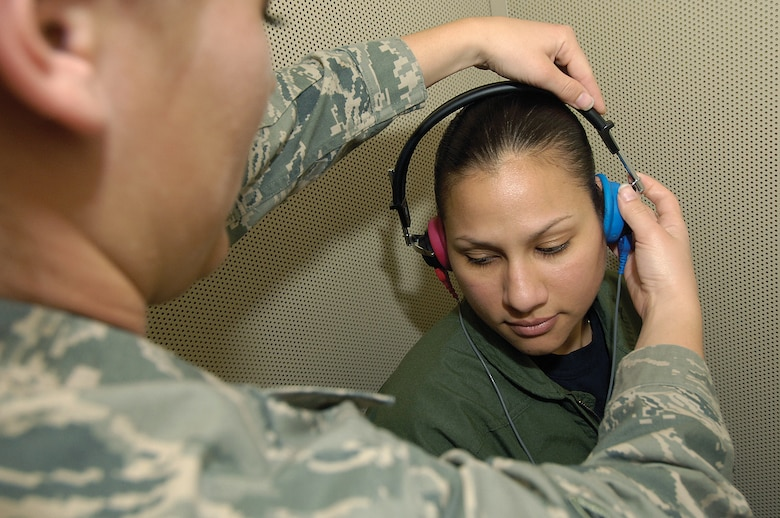 "Airman 1st Class Angia Camp adjusts earphones before a hearing test in an audiology testing booth of the Public Health Flight. The flight handles everything ""from AIDS to zucchini"" says commander Maj. Juan Ramirez, of their responsibilities. The fight acts similarly to a state health department and works jointly with off base agencies in tracking and reporting health information. They have been a focal point for base H1N1 vaccinations, check food safety in all base establishments, monitor mosquito populations here and even do a ""tick drag"" at the Glenwood Training Area to tell where to spray before exercises. (Air Force photo by Margo Wright)"