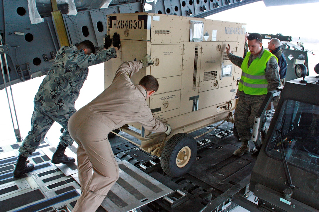 Airmen from the multinational Heavy Airlift Wing move equipment March 30, 2010, in preparation for shipment to units in Afghanistan. HAW Airmen have moved more than 2.1 million pounds of war reserve material essential to surge operations supporting the International Security Assistance Force in Afghanistan. The HAW, based at Papa Air Base, Hungary, operates three C-17 Globemaster III aircraft independently of NATO's military command and comprises 12 nations that activated the unit July 27, 2009. (HAW photo/Finnish Capt. Juha Miettinen)