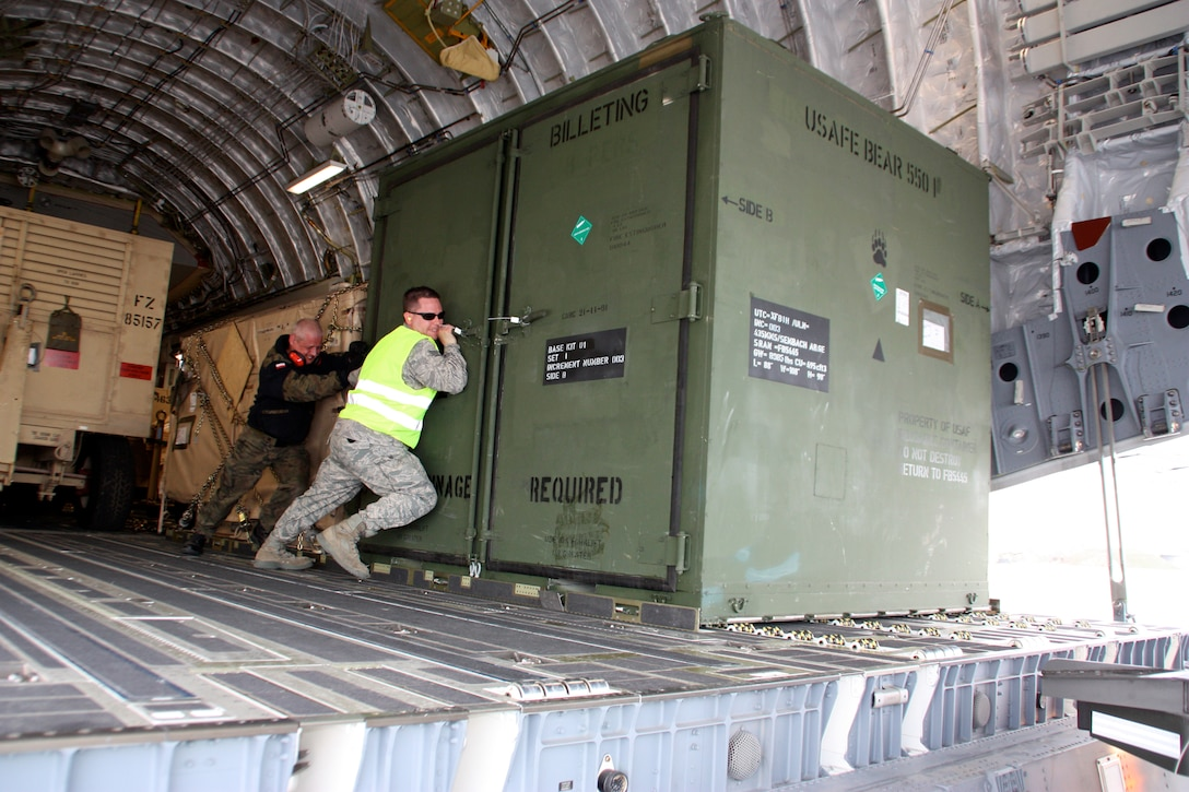 Airmen from the multinational Heavy Airlift Wing move a billeting kit March 30, 2010, in preparation for shipment to units in Afghanistan. HAW Airmen have moved more than 2.1 million pounds of war reserve material essential to surge operations supporting the International Security Assistance Force in Afghanistan. The HAW, based at Papa Air Base, Hungary, operates three C-17 Globemaster III aircraft independently of NATO's military command and comprises 12 nations that activated the unit July 27, 2009. (HAW photo/Finnish Capt. Juha Miettinen)