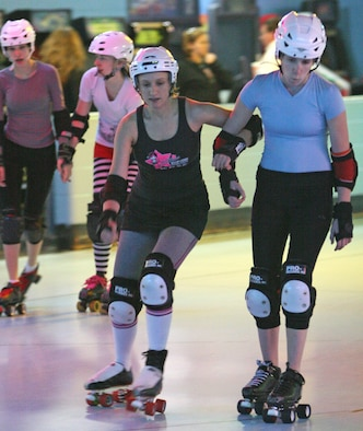 Nicole Messinger, left, blocks out a teammate during a Victory Dolls practice. Messinger joined the team in 2008 and took the leap into the world of roller derby. (Air Force photo by John Stuart)