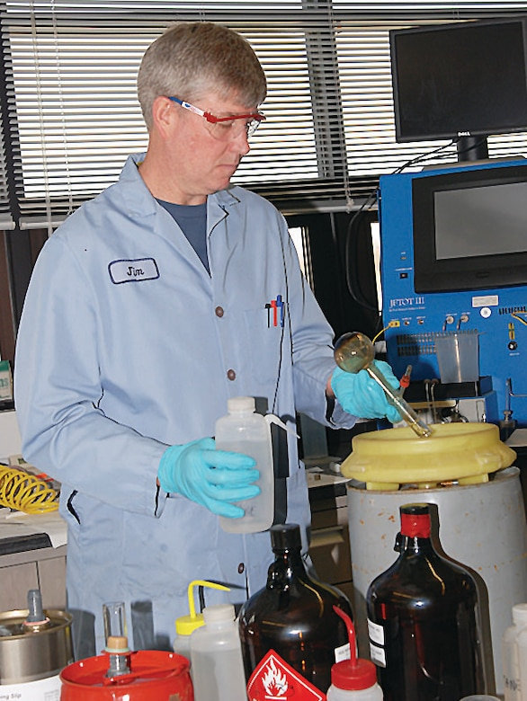 Quality Assurance Specialist James LaFave at the Air Force Petroleum Office cleans a distillation flask after working with JP-8 fuel. A DOD Live Bloggers Roundtable held March 25 featured experts who discussed first test flight of an A-10C Thunderbolt II powered by a blend of Hydro-treated Renewable Jet biofuel, or HRJ, and JP-8 at Eglin AFB, Fla. (U.S. Air Force photo/Bonnie White)