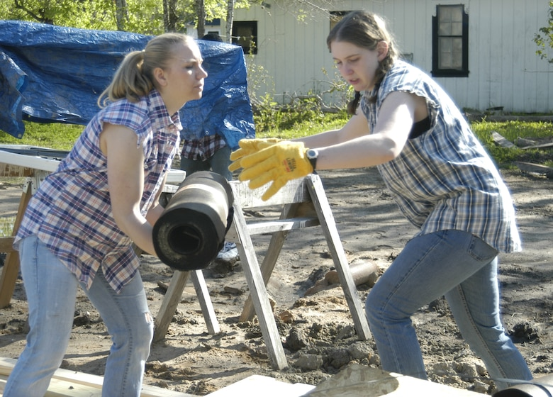Cadet 3rd Class Sarah Sauter of Cadet Squadron 16 and Cadet 2nd Class Bridget Flatley of CS 37 work in muddy terrain while building a house as part of a Habitat for Humanity project March 22, 2010, in Victoria, Texas. (U.S. Air Force photo/John Van Winkle)