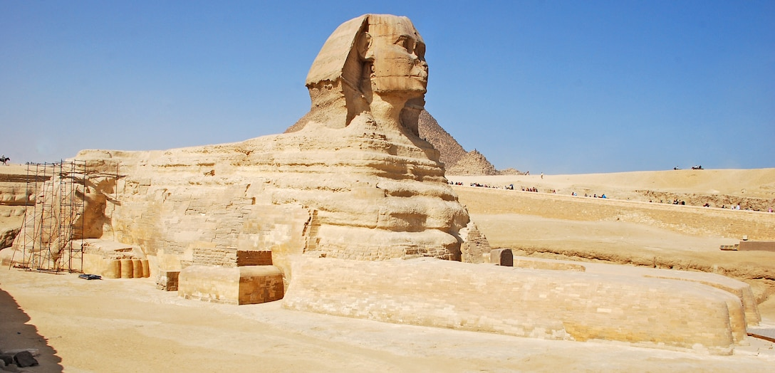 The Great Sphinx of Giza lies on the Giza Plateau with the famous Pyramids of Giza just in the distance, near Cairo, Egypt. The Sphinx is a statue of a reclining lion with a human head that is believed to have been built by ancient Egyptians between 2555 B.C. and 2523 B.C. It is one of the most famous and recognizable pieces of history in the Cairo area. (U.S. Air Force photo/Senior Airman Sara Csurilla)