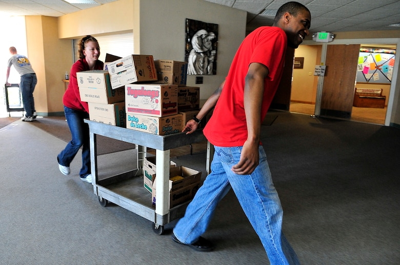 BUCKLEY AIR FORCE BASE, Colo. -- Staff  Sgt. Kristen Porter, Air Force Technical Applications Center  Detachment 45, left, and Senior Airman Darnell Walcott, 460th Space Communications Squadron program manager, volunteer for Hearts Across the Miles March 14. Sergeant Porter and Airman Walcott helped package more than 300 cases of cookies for deployed U.S. troops in Iraq and Afghanistan. (U.S. Air Force photo by Staff Sgt. Kathrine McDowell)