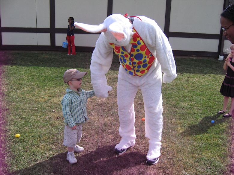 """Johnathon Miller, son of Maj. Greg Miller and Lt. Col. Deanna Miller meets the Easter bunny during a recent Easter party held here on base.  """"This was Johnathon's very first Easter egg hunt,"""" said Lt. Col. Deanna Miller, 107th member.  """"He really enjoyed it, especially meeting the Easter Bunny,"""" she added. More than 150 children of 107th and 914th Airlift Wing members took advantage of the unseasonably warm weather for the annual Easter egg hunt.(U.S. Air Force photo/Lt. Col. Deanna Miller)"""