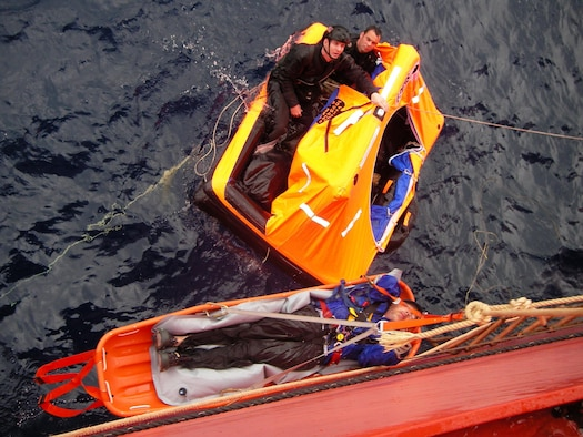 Pararescuemen from the 129th Rescue Wing transfer a patient to a container vessel April 2, 2010. The Eleventh Coast Guard District Rescue Coordination Center used their Automated Mutual Assistance Vessel Rescue system to divert a Liberian registered merchant vessel, the CAP PALMERSTON, enroute to Ensenada, Mexico, to rendezvous with the sailing vessel and pick-up the PJs and their patient. The AMVER program is sponsored by the U.S. Coast Guard and is a voluntary global ship reporting system used worldwide by search and rescue authorities to arrange for assistance to persons in distress at sea. Following the transfer of the patient and PJs from the small sailboat to the CAP PALMERSTON, the ship set course to San Diego. The patient and PJs were picked up by 129th rescue crews April 4, 2010. (Photo courtesy of the CAP PALMERSTON crew.)