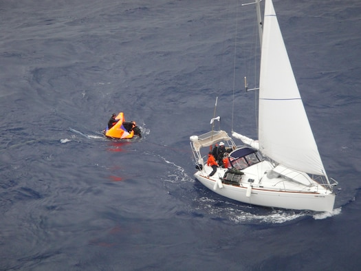 Pararescuemen from the 129th Rescue Wing transfer a patient from a sailboat to a small raft in preparation for transfer to a container vessel April 2, 2010. The Eleventh Coast Guard District Rescue Coordination Center used their Automated Mutual Assistance Vessel Rescue system to divert a Liberian registered merchant vessel, the CAP PALMERSTON, enroute to Ensenada, Mexico, to rendezvous with the sailing vessel and pick-up the PJs and their patient. The AMVER program is sponsored by the U.S. Coast Guard and is a voluntary global ship reporting system used worldwide by search and rescue authorities to arrange for assistance to persons in distress at sea. Following the transfer of the patient and PJs from the small sailboat to the CAP PALMERSTON, the ship set course to San Diego. The patient and PJs were picked up by 129th rescue crews April 4, 2010. (Photo courtesy of the CAP PALMERSTON crew.)