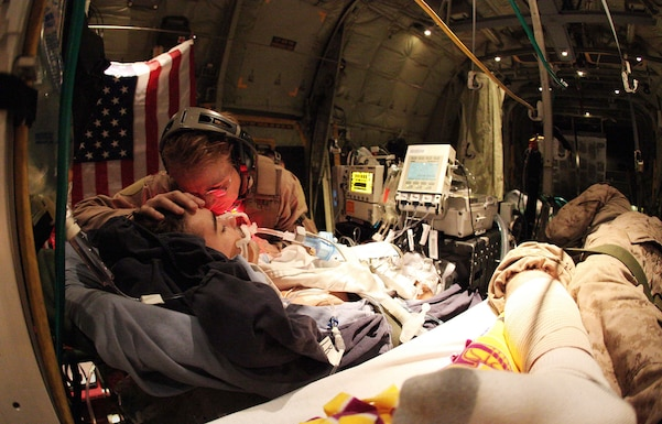 Then- U.S. Air Force Maj. Debora Lehker, a reserve critical care air transport team nurse, comforts a wounded Canadian army soldier aboard a C-130 Hercules during an emergency airlift from Kandahar Airfield, Afghanistan, Feb. 14, 2010. (Courtesy photo)
