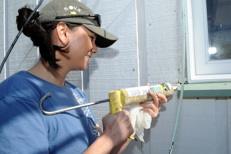 FORT FISHER RECREATION AREA, N.C. -- Lt. Col. Debra Lovette uses a caulking gun to seal the creases of newly installed siding around the window of a cottage here, April 7, 2010. Caulking provides thermal insulation, controls water penetration and reduces noise. Colonel Lovette is the 4th Force Support Squadron commander at Seymour Johnson Air Force Base. She hails from Kinston. (U.S. Air Force photo/Staff Sergeant Courtney Richardson)