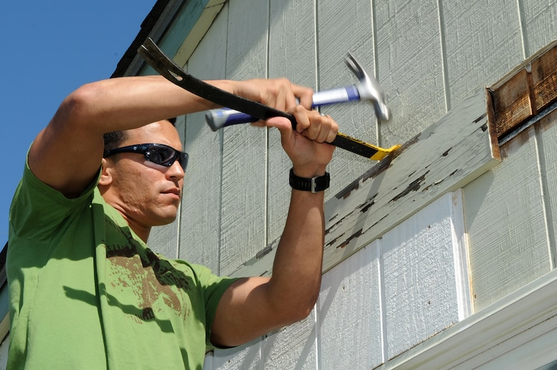 FORT FISHER RECREATION AREA, N.C. -- 2nd Lt. Ralph Soto uses a crow bar to remove weathered wood from a cottage here, April 7, 2010. Airmen from Seymour Johnson Air Force Base volunteered to help replace the siding of cottages here to save money. Lieutenant Soto, 4th Comptroller Squadron financial services flight officer, hails from Chicago. (U.S. Air Force photo/Staff Sergeant Courtney Richardson)