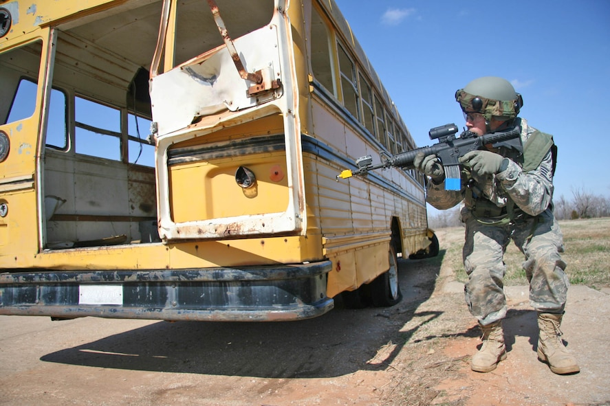 Staff Sgt. Jarod Williams with the 3rd Combat Communications Group peers around a school bus used for cover from enemy fire during a combat training exercise at Tinker's Glenwood Training Area March 17. Airmen from the 3rd Herd, and four other communications groups from Air Force Space Command, will participate in a combat competition here April 16-19.