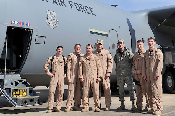 """Airman 1st Class Andrew Nelson, 41st Airlift Squadron loadmaster; Michael Ezell, 19th Aircraft Maintenance Squadron crew chief instructor; Capt. Bret Echard, 41st AS pilot; Col. Greg Otey, 19th Airlift Wing commander; Airman 1st Class Shawn Salefske; 19th AMXS crew chief; Staff Sgt. Thomas Grover, 41st AS loadmaster; and Capt. David Milodragovich, 41st AS pilot; return Feb. 23 from an """"iron swap"""" mission to Kandahar, Afghanistan. Colonel Otey joined the mission to experience the teamwork that goes into mobilizing Combat Airlifters. Iron swaps are conducted to return aircraft to station that require maintenance and inspections not available in a deployed environment. (U.S. Air Force photo by Senior Airman Christine Clark)"""