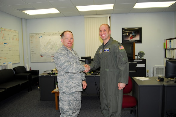 Col. Craig Berlette, 43rd Airlift Wing Vice Wing Commander, presents the Commander's Coin to Capt. Nate Cook, 43rd AW, on behalf of Col. James Johnson, 43rd AW Commander, April 6. Captain Cook is the Chief of Wing Plans and Inspections. (U.S. Air Force photo/2nd Lt. Cammie Quinn)