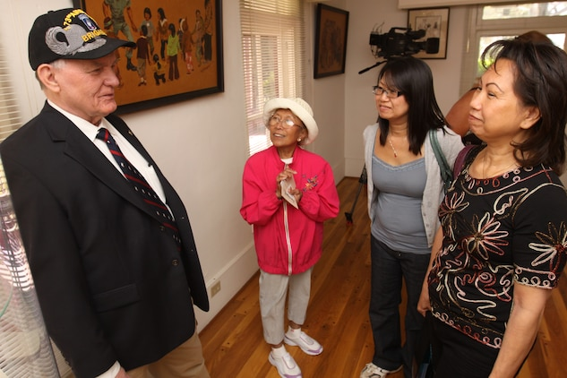"""Retired Gunnery Sgt. Lewis D. Beatty (left), talks with Vietnam War survivors during the opening of Camp Pendleton's """"Images at War's End"""" exhibit at the Santa Margarita Ranch House, April 8. After the fall of Saigon in 1975, nearly half of the 130,000 Vietnamese refugees that resettled in America passed through the gates of Camp Pendleton. Thirty-five years later, base historians are now honoring their story with the museum exhibit, a 36-photo display that commemorates the lives of those who fled North Vietnamese communist oppression."""