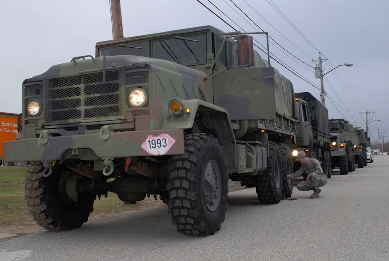 Senior Airman Christopher Devine inspects the wheel of his light medium tactical vehicle as the 103rd Air Control Squadron prepares to convoy back to Orange, Conn. after remaining on alert status at Camp Rell, Niantic, Conn. in support of flood relief March 31, 2010. Part of the 103rd Task Force, Devine's mission capability included using the LMTVs to rescue people trapped because of high waters. (U.S. Air Force photo by Tech. Sgt. Joshua Mead)