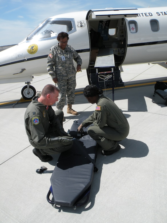 A medical team prepares a table for a patient's arrival at MacDill Air Force Base, Fla. March 8, 2010. The patient will be transferred to the table which is then loaded in the aircraft on a slide and onto a special medical sled. This, part of the first ever aeromedical evacuation mission for the 103rd Airlift Wing, Conn. Air National Guard. The Flying Yankee C-21s picked up patients as they arrived from overseas as well as those needing transfer from other CONUS medical facilities. (U.S. Air Force Photo by Maj. Christopher P. Papa, photo was altered for security purposes)