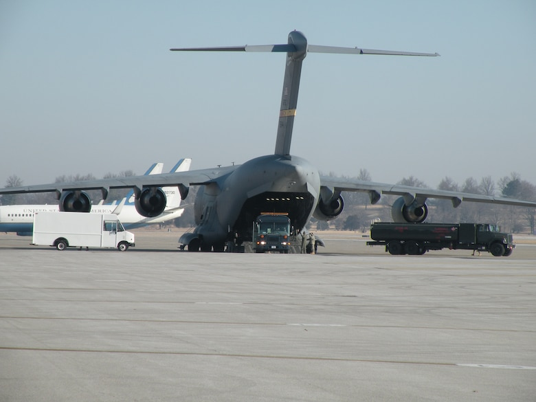 Patients are offloaded from an arriving C-17 Globemaster and into waiting vehicles on the flightline at Scott Air Force Base March 6, 2010. Two ambulatory patients from this flight were loaded into a waiting C-21A aircraft marking the historic first aeromedical evacuation flight for the 103rd Airlift Wing, Conn. Air National Guard. (U.S. Air Force photo by Maj. Christopher P. Papa)