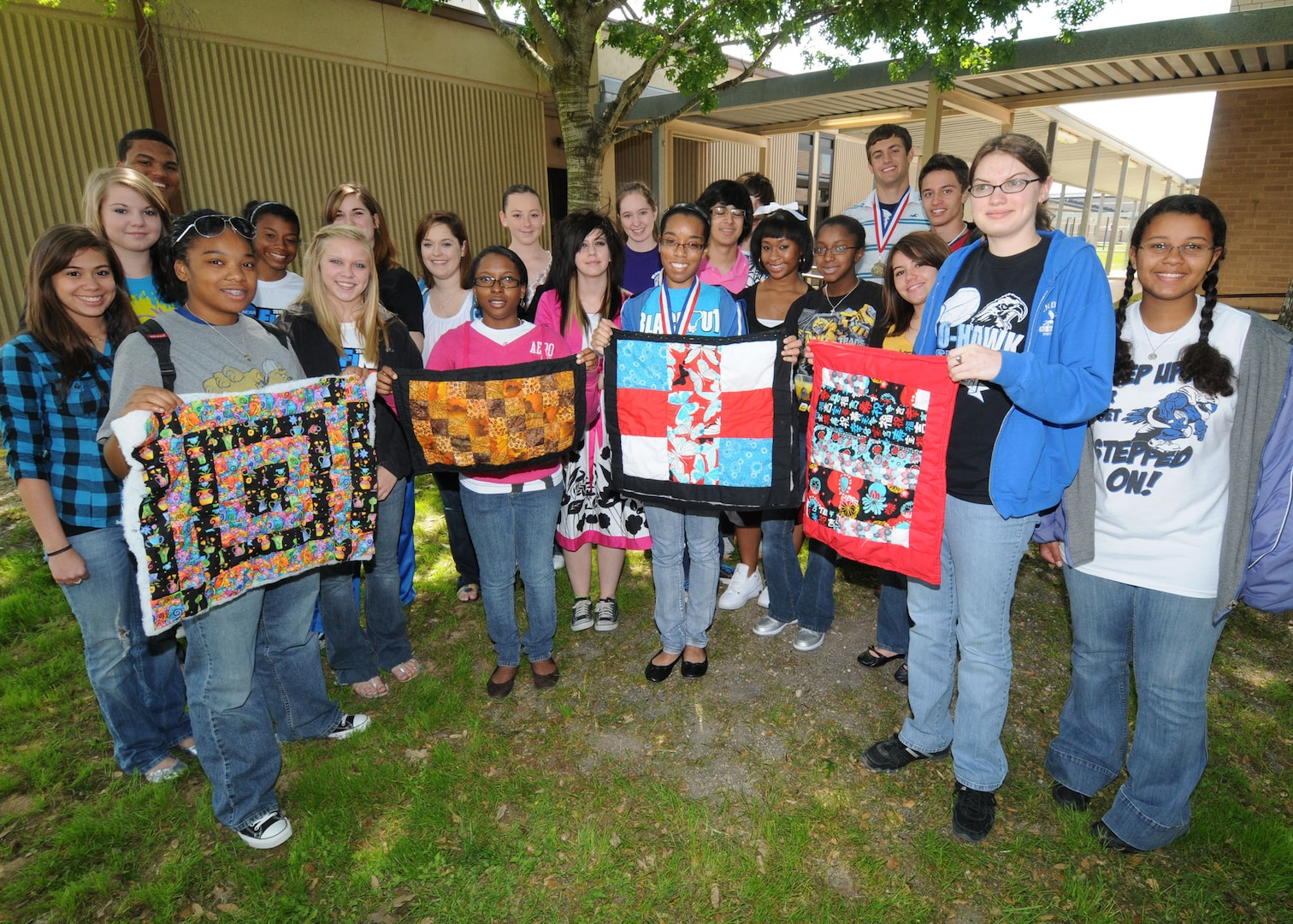 Students at Randolph Air Force Base High School display quilt samples made during a quilting project. THe students made larger quilts to donate to Project Linus for traumatized children. The quilting was done under the direction of RHS teacher Shirley McMenamin. (U.S. Air Force photo by Dave Terry)