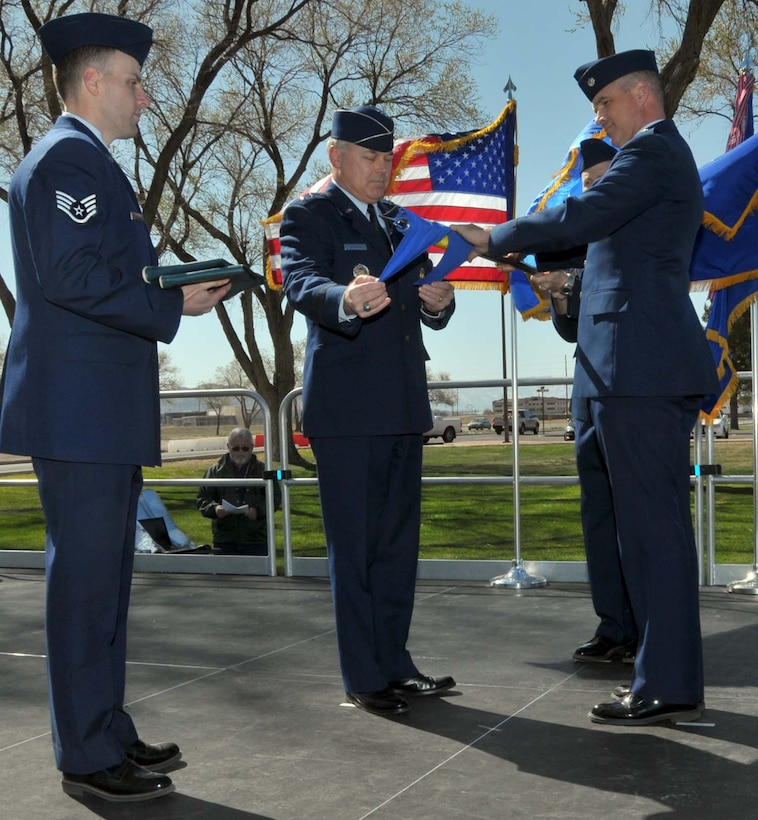 Maj. Gen. Stephen T. Sargeant, Air Force Operational Test and Evaluation Center Commander, furls the AFOTEC Detachment 3 flag with help from Lt. Col. Christopher A. Hawes, AFOTEC Det. 3 Commander, and SSgt. Justin Schoenthal during an April 5 inactivation ceremony at Kirtland Air Force Base, N.M.