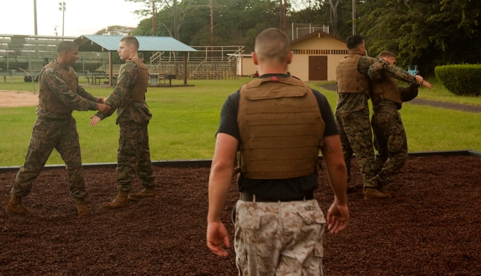 (Center) Sgt. Joseph M. Benezette, a Marine Corps Martial Arts instructor trainer with U.S. Marine Corps Forces, Pacific, observes Marines as they practice shoulder throws during green belt training April 11 at Bordelon Field, Camp H. M. Smith, Hawaii. Benezette has taken the challenging of training 80 percent of Headquarters and Service Battalion, MarForPac, to green belt before August.