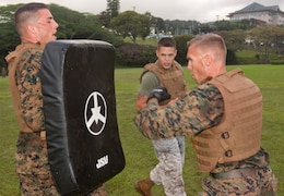 (Center) Sgt. Robert J. Porras, a Marine Corps Martial Arts instructor with U.S. Marine Corps Forces, Pacific, leads two Marines in combat conditioning drills during  green belt training April 11 at Bordelon Field, Camp H. M. Smith, Hawaii. Porras has taken the challenging of training 80 percent of Headquarters and Service Battalion, MarForPac, to green belt before August.