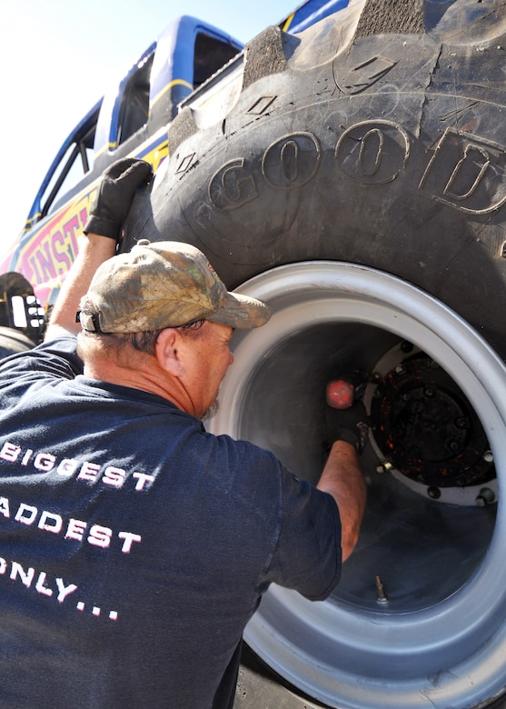 "Lionel Easler tightens down the lugs on ""monster"" tires of his truck ""The Instigator,"" April 9 in preparation for the weekend airshow at Eglin Air Force Base, Fla.  The truck was on display with the Air Force Reserve recruiting booth.  Mr. Easler has been driving monster trucks for five years and competes in about 35 truck shows a year.  This was the first airshow however for the Florida native.  (U.S. Air Force photo/Tech. Sgt. Samuel King Jr.)(U.S. Air Force photo/Tech. Sgt. Samuel King Jr.)"