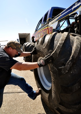 "Lionel Easler kicks the ""monster"" tires into place on his truck ""The Instigator,"" April 9 in preparation for the weekend airshow at Eglin Air Force Base, Fla.  The truck was on display with the Air Force Reserve recruiting booth.  Mr. Easler has been driving monster trucks for five years and competes in about 35 truck shows a year.  This was the first airshow however for the Florida native.  (U.S. Air Force photo/Tech. Sgt. Samuel King Jr.)"