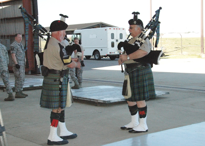 """Pipe Sgt. Bob Andruss (left) and Pipe Maj. Bob Horner of the Destin-based 23rd Highlanders pipe and drum band play """"Scotland the Brave"""" on the tarmac at Hurlburt Field April 6.  The musicians volunteered to perform during Operation Homecoming, an event that reunited returning Duke Field and Hurlburt warfighters with family, fellow Airmen and local civic leaders following lengthy deployments in support of operations in Southwest Asia. (U.S. Air Force photo/Dan Neely)"""