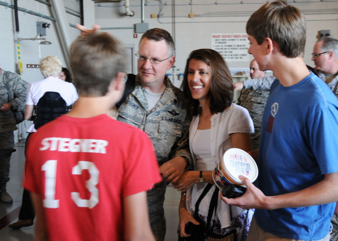 Air Force Reserve Lt. Col. Christopher Stegner from Duke Field's 711th Special Operations Squadron, is welcomed home by his sons Evan (left) and Andrew and wife Jennifer inside a hangar at Hurlburt Field April 6. Known as Operation Homecoming, the event reunited returning Duke Field and Hurlburt warfighters with family, fellow Airmen and local civic leaders following lengthy deployments in support of operations in Southwest Asia. (U.S. Air Force photo/Adam Duckworth)
