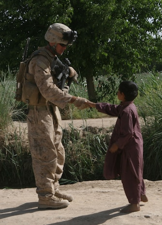 A Marine with 1st Battalion, 6th Marine regiment shakes a young boys hand while out on patrol in Marjah Afghanistan, April 13. Marines and Afghan National Army soldiers with 1/6 are taking part in the Marjah Accelerated Agricultural Transition program, which is a project aimed at facilitating the transition from illicit to licit crops.