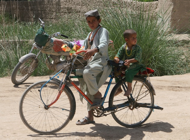 Two Afghan boys ride their bike through the bazaar in Marjah Afghanistan, April 13. Marines and Afghan National Army soldiers with 1st  Battalion, 6thMarine Regiment are taking part in the Marjah Accelerated Agricultural Transition program, which is a project aimed at facilitating the transition from illicit to licit crops.