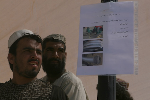 Two men who came to sign up for the Marjah Accelerated Agricultural Transition program, stand near a sign which gives details about what farming equipment and tools participants will receive upon meeting the requirements of the project, at the government center in Marjah, Afghanistan, April 13. Marines and Afghan National Army soldiers with 1st Battalion, 6th Marine Regiment are taking part in the Marjah Accelerated Agricultural Transition program, which is a project aimed at facilitating the transition from illicit to licit crops.