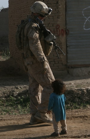 A Marine passes an Afghan child asking for food and water, while on a foot patrol near the government center in Marjah, Afghanistan, April 13. Marines and Afghan National Army soldiers with 1st Battalion, 6th Marine Regiment are taking part in the Marjah Accelerated Agricultural Transition program, which is a project aimed at facilitating the transition from illicit to licit crops,
