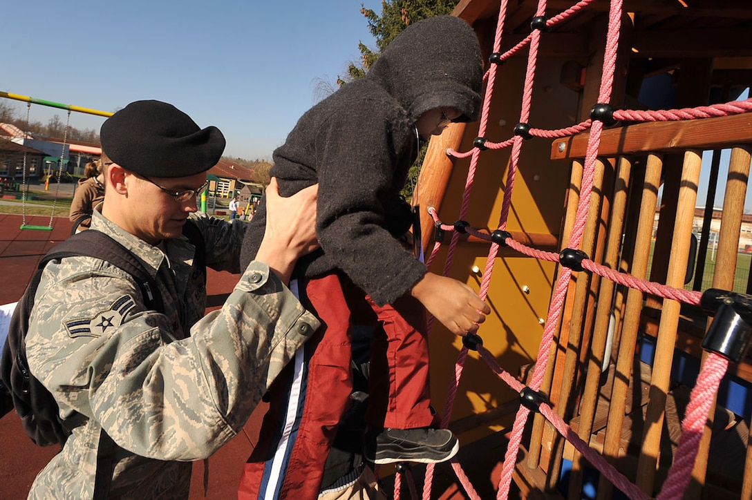 """Airman 1st Class Brian Crabill gives a child a boost up on the playground during """"Boot Camp Week"""" April 7, 2010, at the child development center at Rose Barracks, Vilseck Military Community, Germany. """"Boot Camp Week"""" gave servicemembers' children an opportunity to experience some military norms such as physical training, first aid, land navigation and tactical vehicle familiarization in support of the Department of Defense's Month of the Military Child. Airman Crabill is a 2nd Air Support Operations Squadron tactical air control party member. (U.S. Air Force photo/Senior Airman Tony R. Ritter)"""